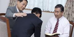Trưởng lão đang dùng Kinh Thánh để giúp một người