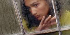 A lonely young woman looking out a window