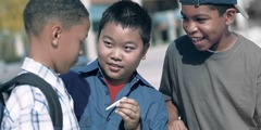 Two young boys offering someone a cigarette