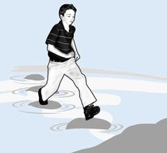 Ein Junge springt von Stein zu Stein, um übers Wasser zu kommen