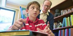 Maestro mirando por encima del hombro de un estudiante