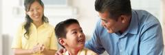 Ein Vater spricht mit seinem Sohn, während die Mutter im Hintergrund zuhört.