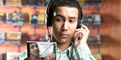 A teenage boy wearing headphones and listening to music as he examines a CD cover.