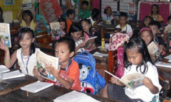 A classroom of children reading My Book of Bible Stories in Pangasinan