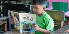 A young boy reading My Book of Bible Stories in Pangasinan