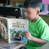 Un neno lendo Mi libro de historias bíblicas en pangasinán