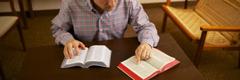 Moški primerja dva svetopisemska prevoda.