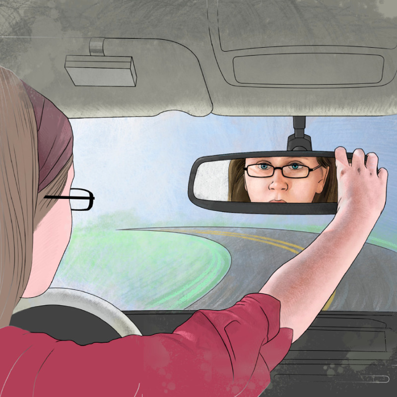 A girl driving a car and looking at herself in the rearview mirror