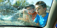 Two young boys looking at a car's windshield broken by their baseball