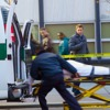 A person is lifted into an ambulance as passersby observe