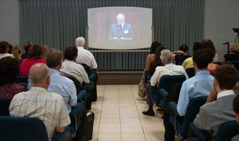 An audience watching the annual meeting program via webcast