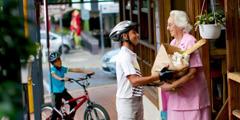 食料品の入った袋を持つ年配の女性を手助けしている少年