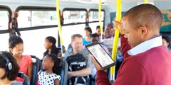 Mies käyttää JW Library -sovellusta mobiililaitteella matkustaessaan julkisella liikennevälineellä