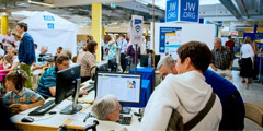 Visitors exploring a stand highlighting the jw.org website