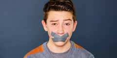 A teenage boy with tape over his mouth to prevent him from cursing