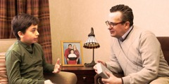A boy sits beside a picture of his family and talks with a man who is holding a Bible