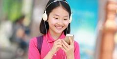 Una joven escucha música en su teléfono