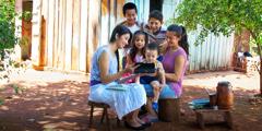 Perhe katsoo videota, jossa käytetään heidän äidinkieltään.