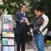 Seorang Saksi Yehuwa yang berdiri di samping rak lektur beroda sedang menyampaikan berita Alkitab kepada seorang pria