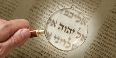 The Tetragrammaton in an ancient manuscript is viewed under a magnifying glass