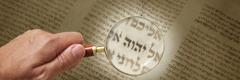 Valaki nagyítóval vizsgálja a tetragramot egy ókori kéziraton