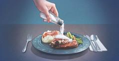 Nekdo stresa veliko soli na krožnik s hrano.