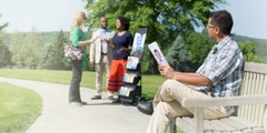 A man holds a tract and observes Jehovah's Witnesses talking to a woman who has approached their witnessing cart