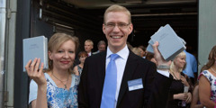 A smiling couple hold up copies of the newly released New World Translation in Estonian