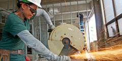Darbininkė diskiniu metalo pjūklu pjausto profiliuočius, kurie bus naudojami biuro sienoms statyti