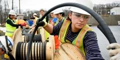 Arbeiterinnen ziehen Stromkabel für die Stromversorgung des Warwick-Komplexes