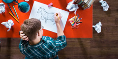 A teenage boy makes many attempts to draw a horse