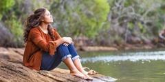 Mladé dievča sedí na brehu jazera