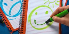 A young person draws a sad face and a happy face