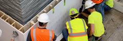 Elektriker, Monteure und andere Mitarbeiter helfen bei der Installation eines beleuchteten Schildes im Foyer