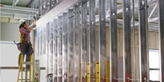 Egy munkás ellenőrzi az elektromos vezetékek csatornáinak távolságát