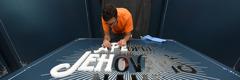 """Припрема знака на улазу у галерију где је постављена изложба """"Народ за Јеховино име"""""""