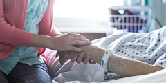 A young woman holds an older person's hand in a hospital