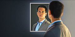 A young man looks at himself in a mirror