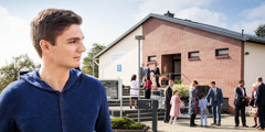 A young man observes people walking into a Kingdom Hall