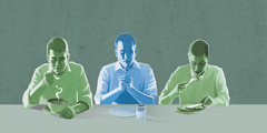 A man prays over an empty plate while men beside him eat