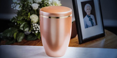 Cremation urn next to a picture of the deceased