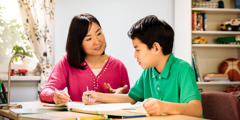 A mother helps her son with his homework