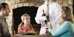 A little girl observes her mother refuse a waiter's offer of more wine