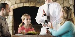 एक छोटी लड़की देख रही है कि उसकी मम्मी वेटर को और वाइन देने से मना कर रही है
