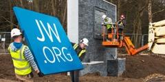 電気技師がサインを新しい英国支部の入口に取り付けている。