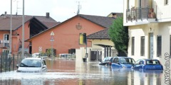 A flooded street near Moncalieri, Italy, with cars partially submerged