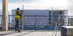 A member of the architectural team uses a tripod-mounted laser level