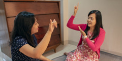 Two women use Indonesian Sign Language to communicate