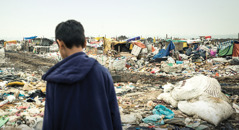 A boy stands in a garbage dump like the one where Israel Martínez lived for three years