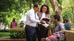 Israel Martínez and his wife preach to a man in a park